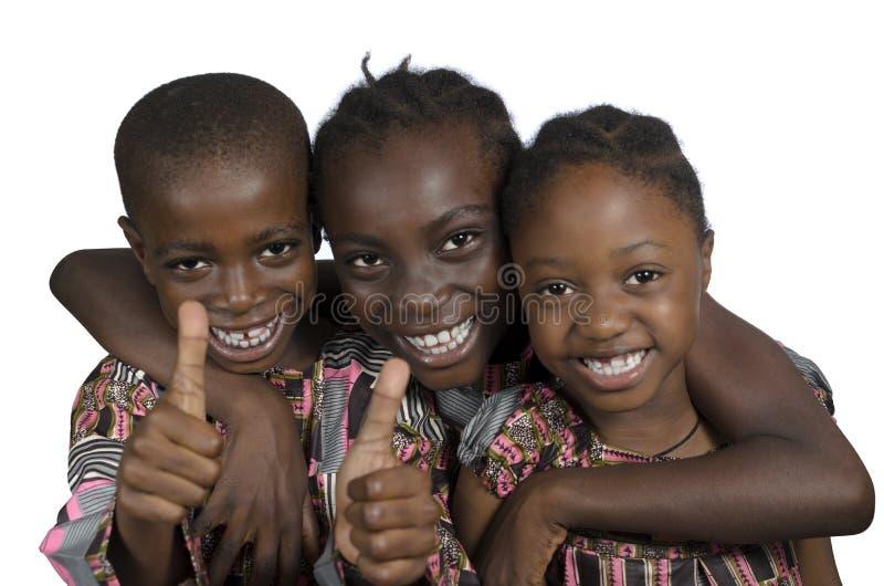 Tre bambini africani che tengono i pollici su fotografia stock