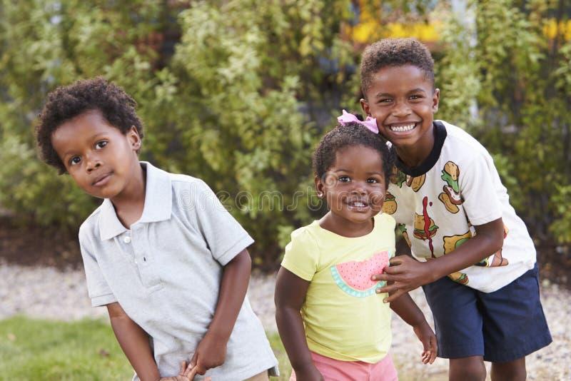Tre bambini afroamericani in un giardino che guarda alla macchina fotografica fotografia stock