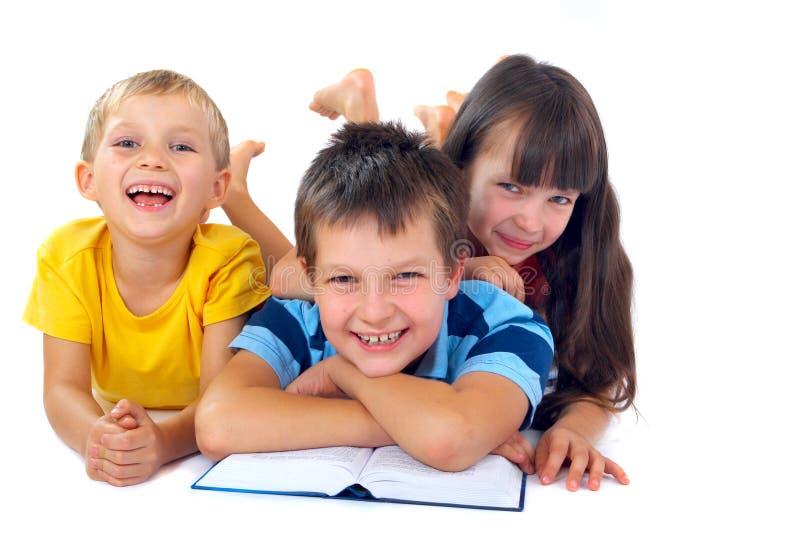 Tre bambini che leggono sul pavimento fotografia stock
