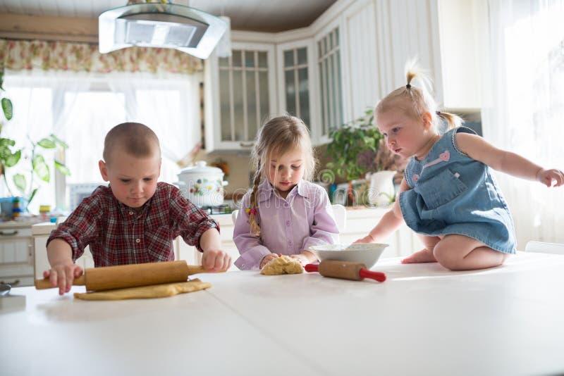Tre bambini che preparano i biscotti nella cucina immagine stock libera da diritti