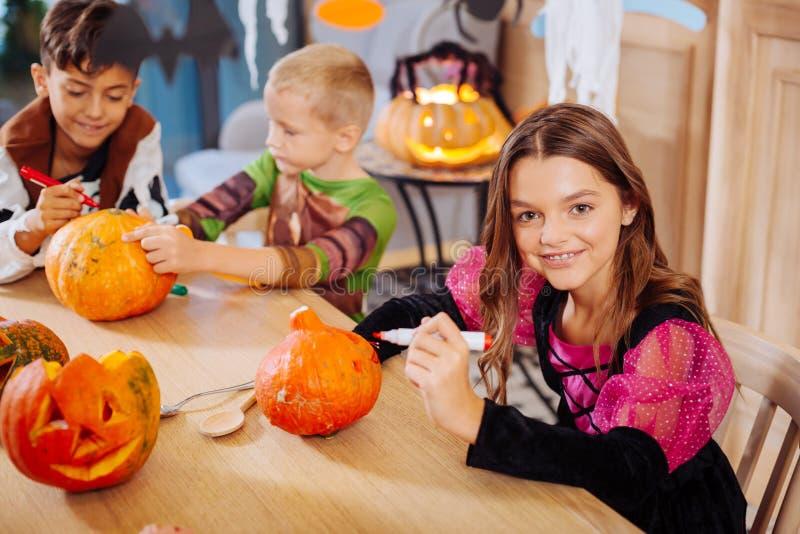 Tre bambini che ritengono addetti a decorare le zucche per il partito di Halloween immagine stock libera da diritti