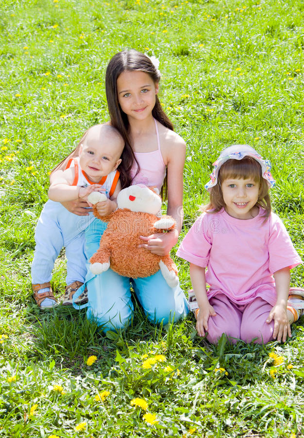 Tre bambini che si siedono sull'erba immagine stock libera da diritti