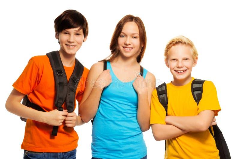 Tre bambini con gli zainhi del banco immagini stock