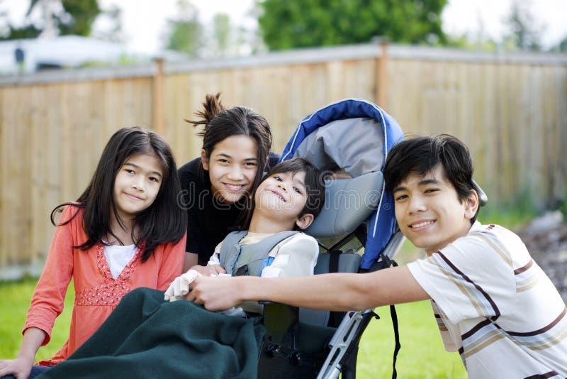 Tre bambini dal fratello invalido in sedia a rotelle immagine stock libera da diritti