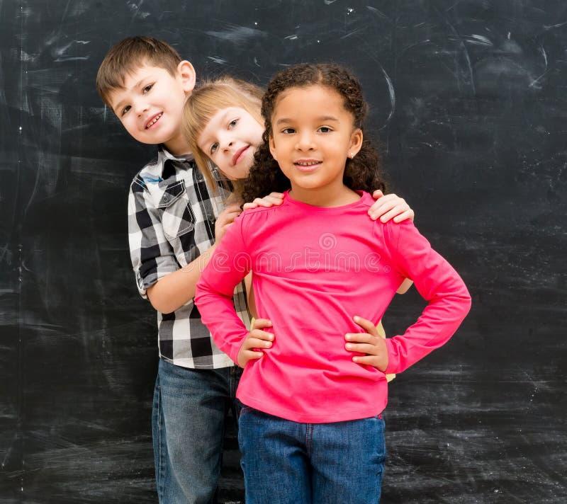 Tre bambini differenti stanno uno per uno dantesi una occhiata fuori da dietro fotografie stock libere da diritti