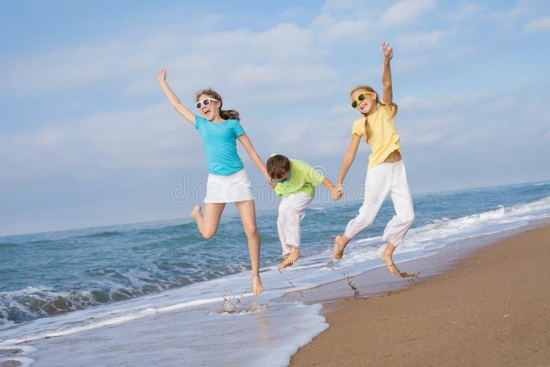 Tre bambini felici che corrono sulla spiaggia al tempo di giorno fotografia stock