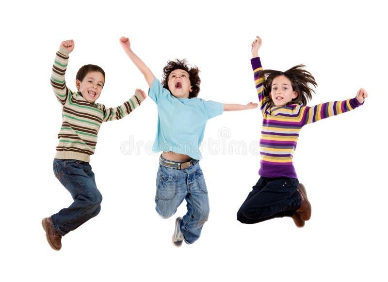 Tre bambini felici che saltano immediatamente fotografia stock