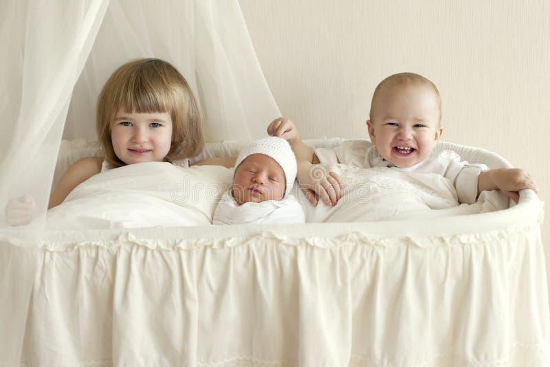 Tre bambini, fratelli e sorelle si siedono in una culla ed in una a bianche immagine stock