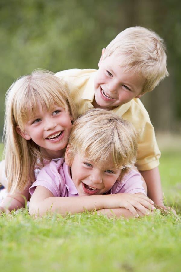 Tre bambini in giovane età che giocano all'aperto sorridere immagini stock libere da diritti