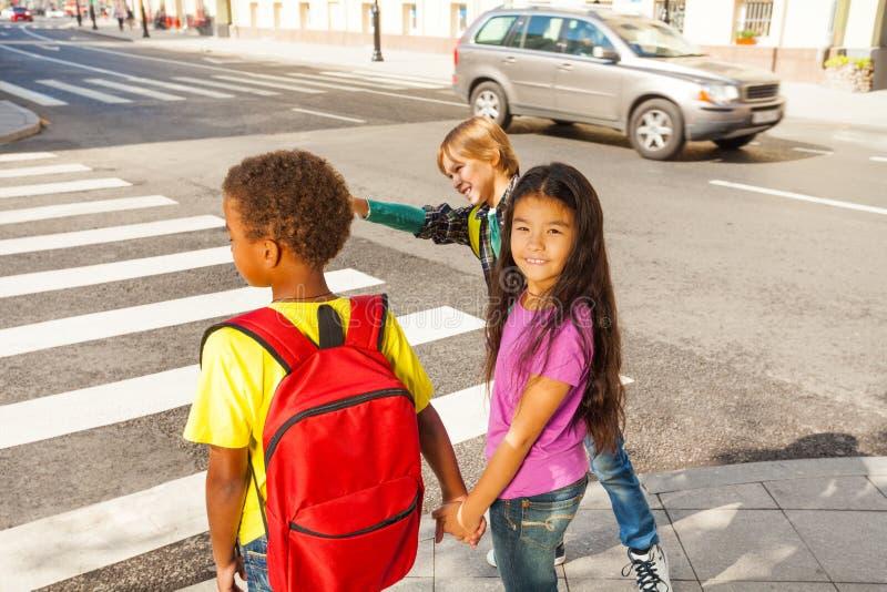 Tre bambini internazionali pronti ad attraversare strada immagine stock libera da diritti