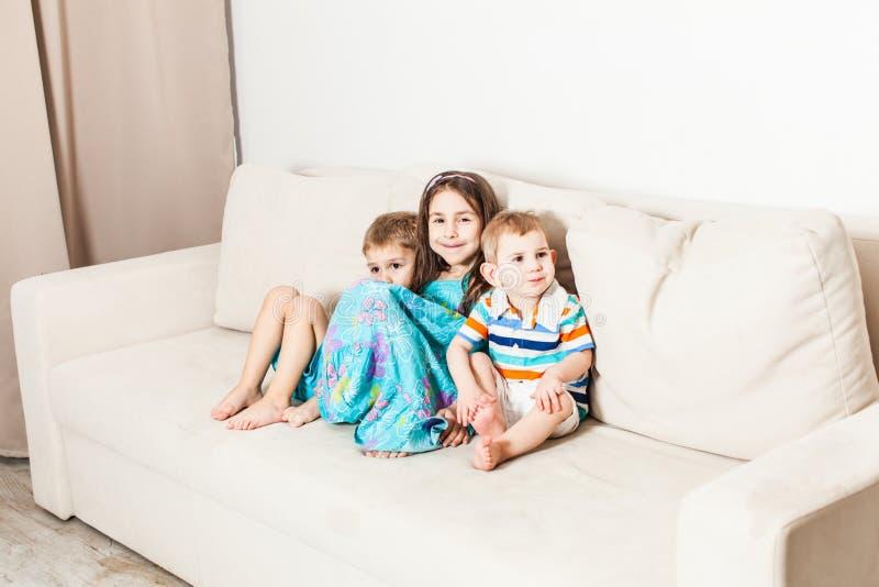 Tre bambini sono seduta fotografata sullo strato fotografia stock libera da diritti