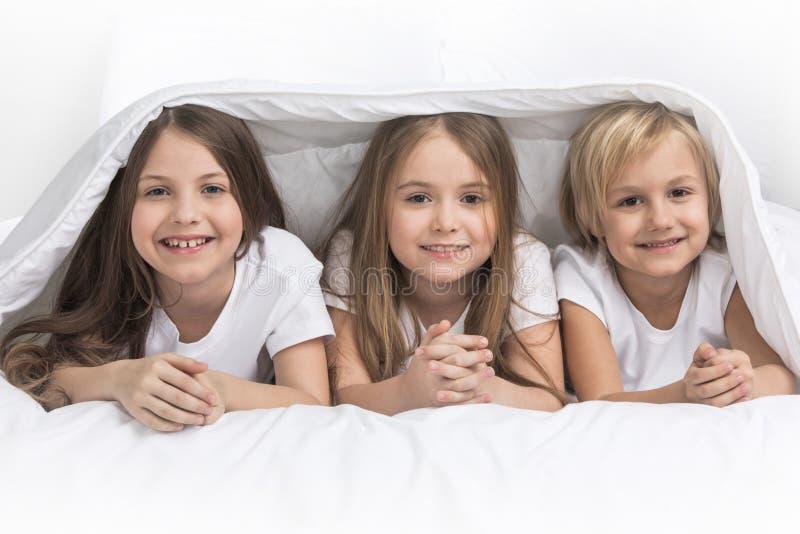 Tre bambini sotto la coperta fotografie stock