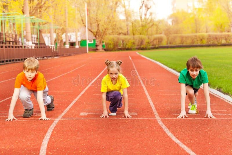 Tre bambini stanno con il ginocchio piegato pronto a funzionare immagini stock