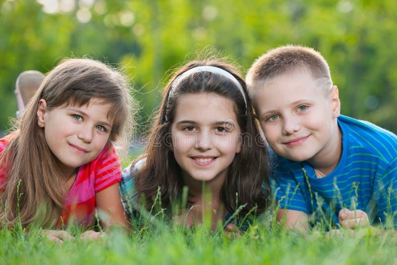 Tre bambini sull'erba fotografie stock libere da diritti