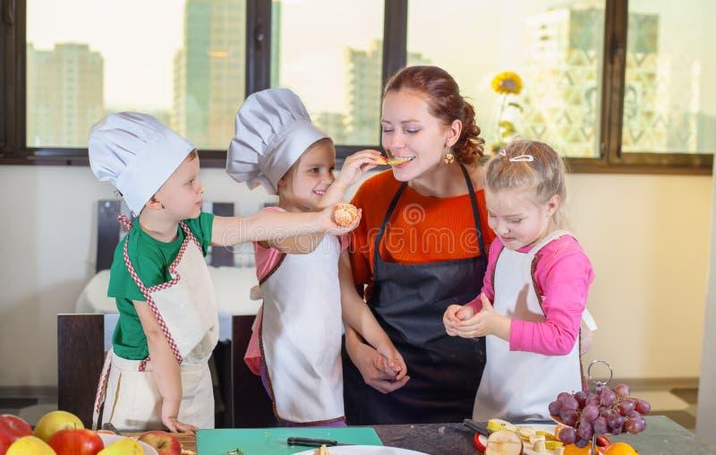 Tre bambini svegli stanno preparando una macedonia in cucina immagini stock
