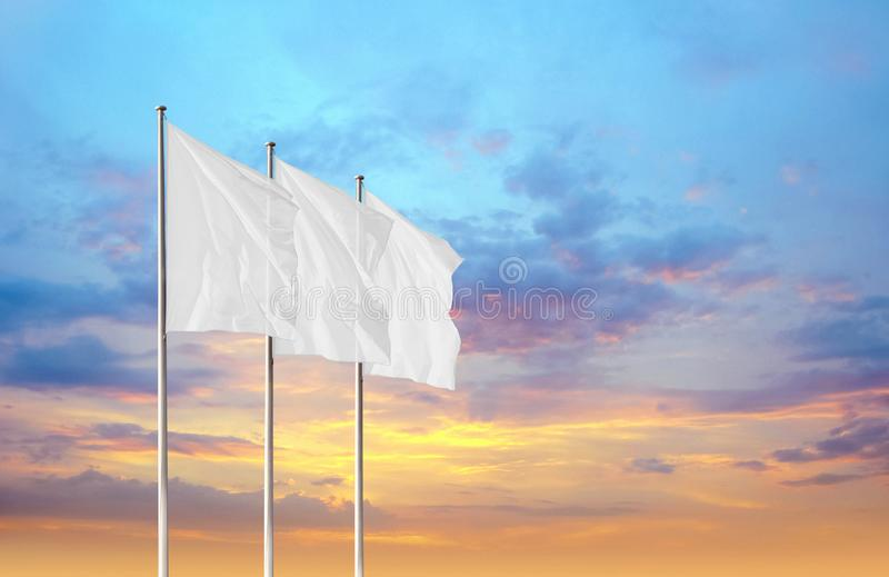 Tre bandiere corporative in bianco bianche che ondeggiano nel vento contro il cielo di tramonto immagini stock libere da diritti