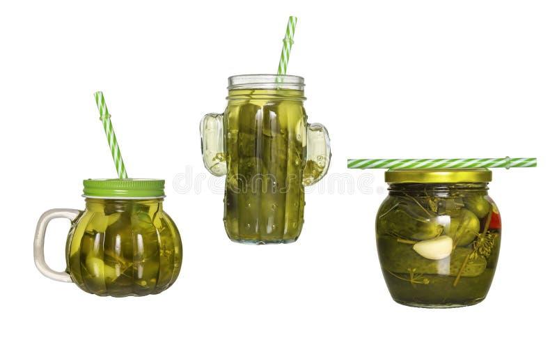 Tre barattoli di vetro con i coperchi ed i tubuli con il cetriolo marinano isolato immagini stock