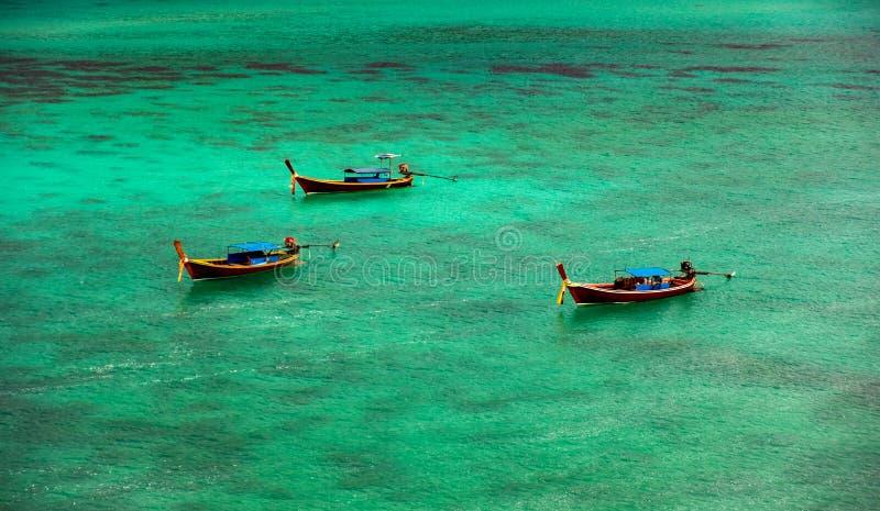 Tre barche fanno galleggiare in chiaro il mare di verde smeraldo, trascurante la barriera corallina subacquea Turisti aspettanti  fotografie stock
