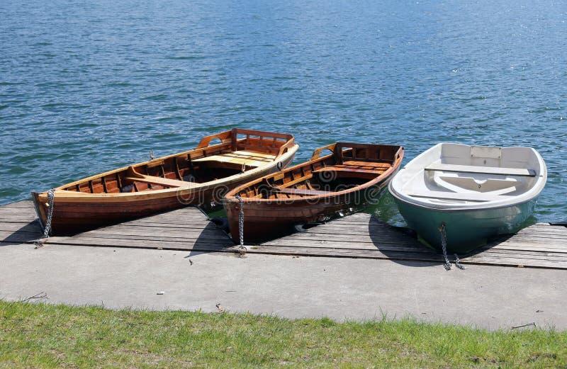 Tre barche a remi attraccate sulla riva del lago fotografia stock