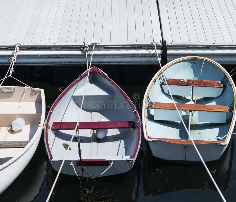Tre barche a remi hanno legato nella linea ad un bacino in Maine immagini stock libere da diritti