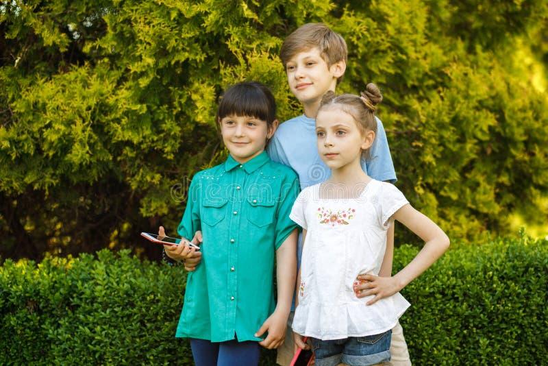 Tre barn av skolaålder har gyckel i natur barngyckel som har arkivfoton