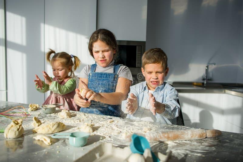 Tre barn förbereder något från degen arkivbild