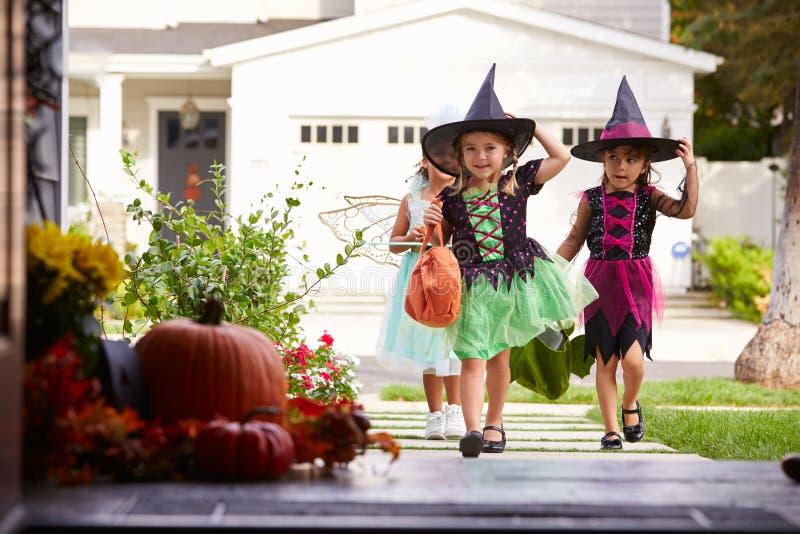 Tre barn i allhelgonaafton kostymerar trick eller behandling royaltyfria foton