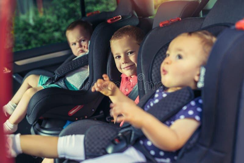 Tre barn i bilsäkerhetsplats fotografering för bildbyråer