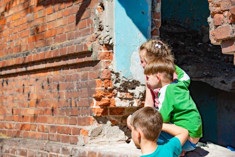 Tre barn i ett förstört hus döljer från militära konflikter, flykting som barn har lidit från förstörelsen av arkivfoto
