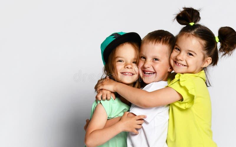 Tre barn i ljus kläder, två flickor och en pojke Trillingar syskongrupp krama på kamera Familjeband kamratskap royaltyfri bild