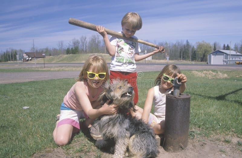 Tre barn med deras hund arkivbild