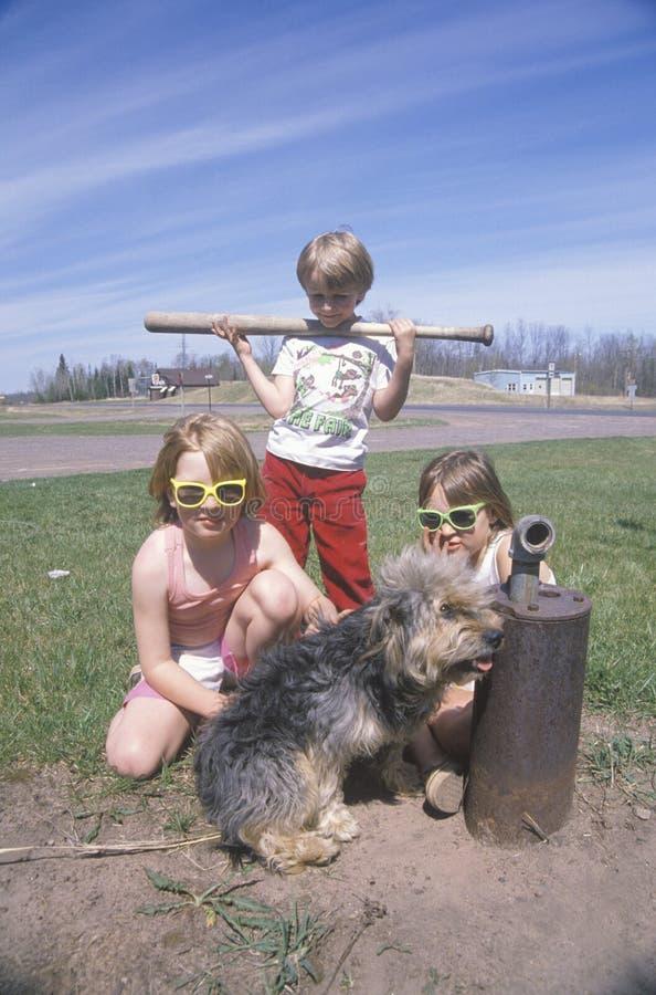 Tre barn med deras hund arkivbilder