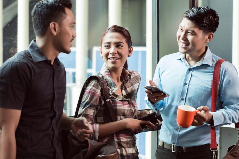 Tre barn och gladlynta anställda på deras arbetsplats som talar i morgonen arkivbilder