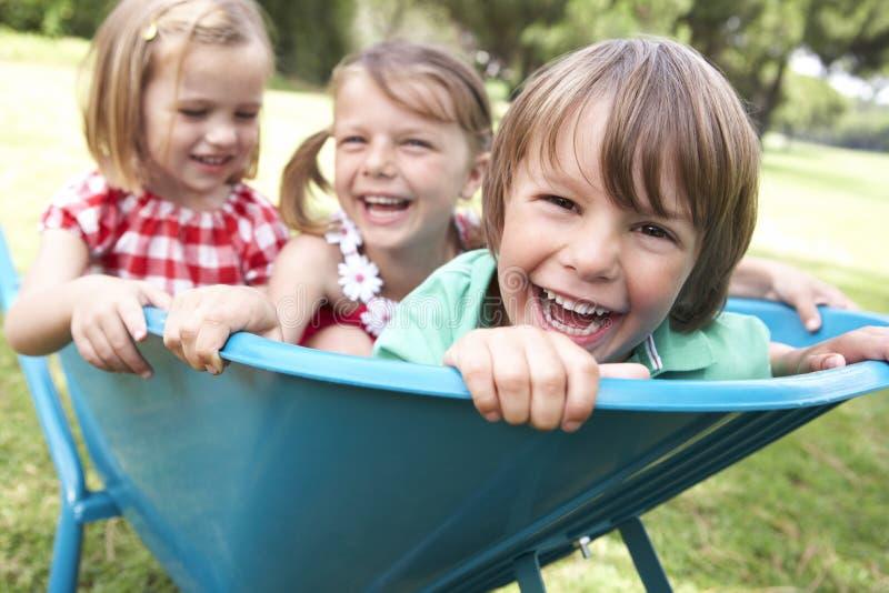 Tre barn som sitter i skottkärra royaltyfri bild