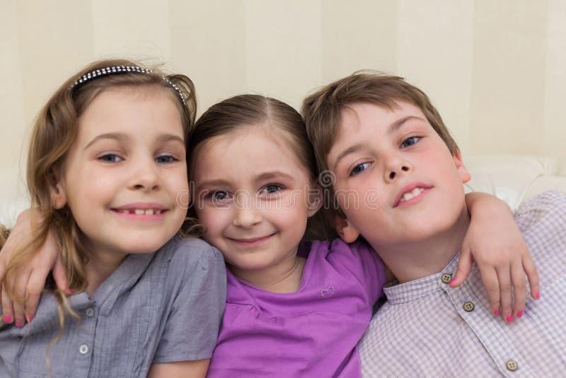 Tre barn som sitter på krama för soffa royaltyfria foton
