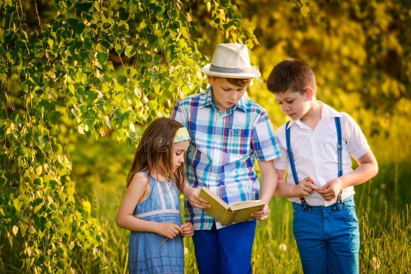 Tre barn som tillsammans läs i sommaren för systerleende för broder head stående skjuten dräkt royaltyfri foto