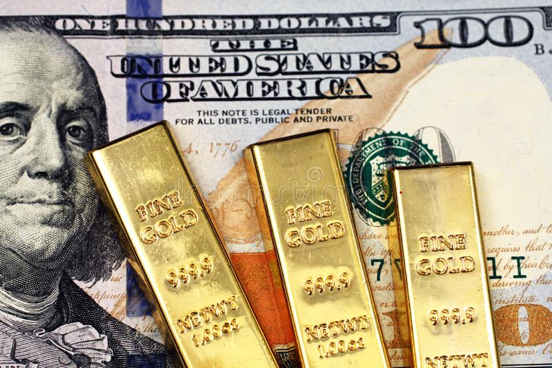 Tre barre di oro con le cento banconote in dollari americana fotografie stock libere da diritti