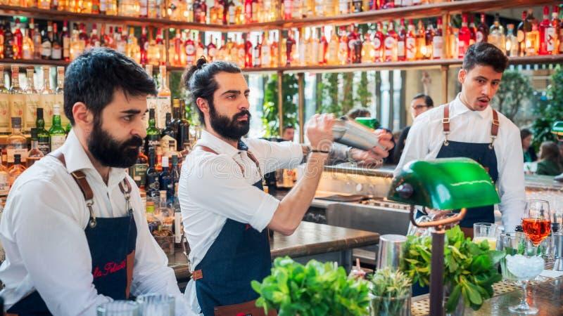 Tre bartendrar som förbereder coctailar i La Felicita Bar, Paris, Frankrike royaltyfria bilder