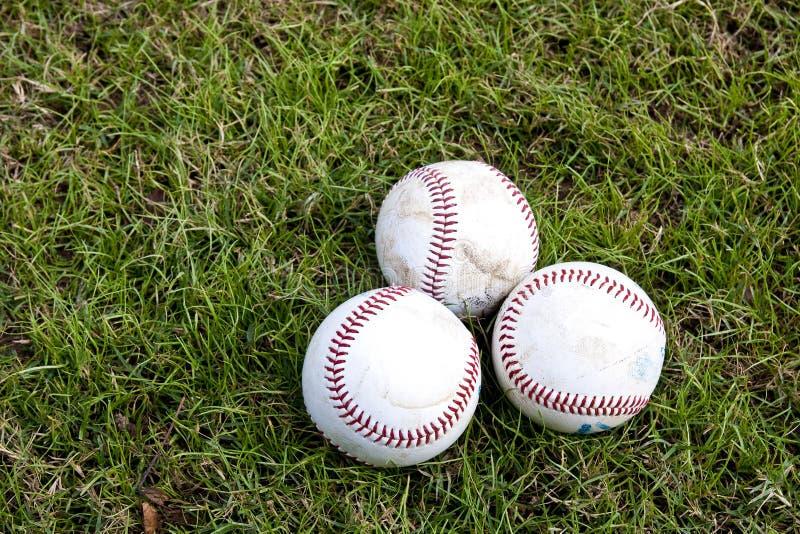 Tre baseball in erba fotografia stock