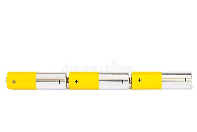 Tre batterie AA sono collegate in un circuito elettrico di serie su un fondo bianco con il percorso tagliato immagine stock libera da diritti