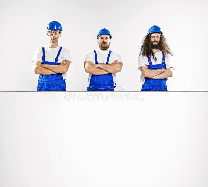 Tre begåvade hantverkare med ett tomt bräde royaltyfria foton