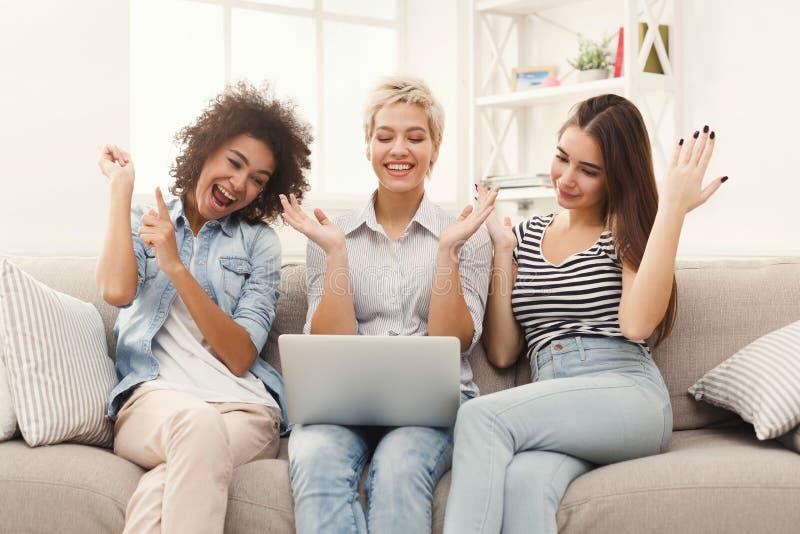 Tre belle donne che per mezzo del computer portatile a casa fotografia stock