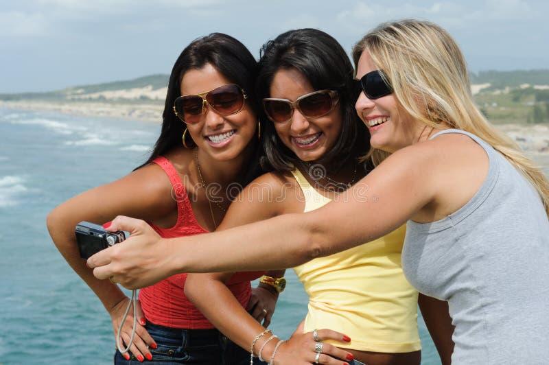 Tre belle donne che prendono selfie sulla spiaggia immagini stock
