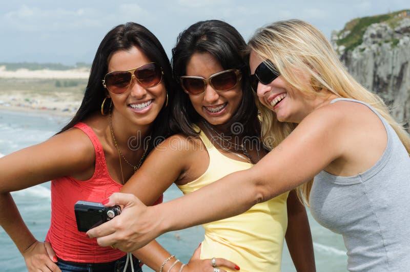 Tre belle donne che prendono selfie sulla spiaggia fotografia stock