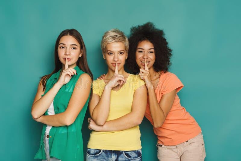 Tre belle donne che tengono le dita alle labbra fotografia stock libera da diritti