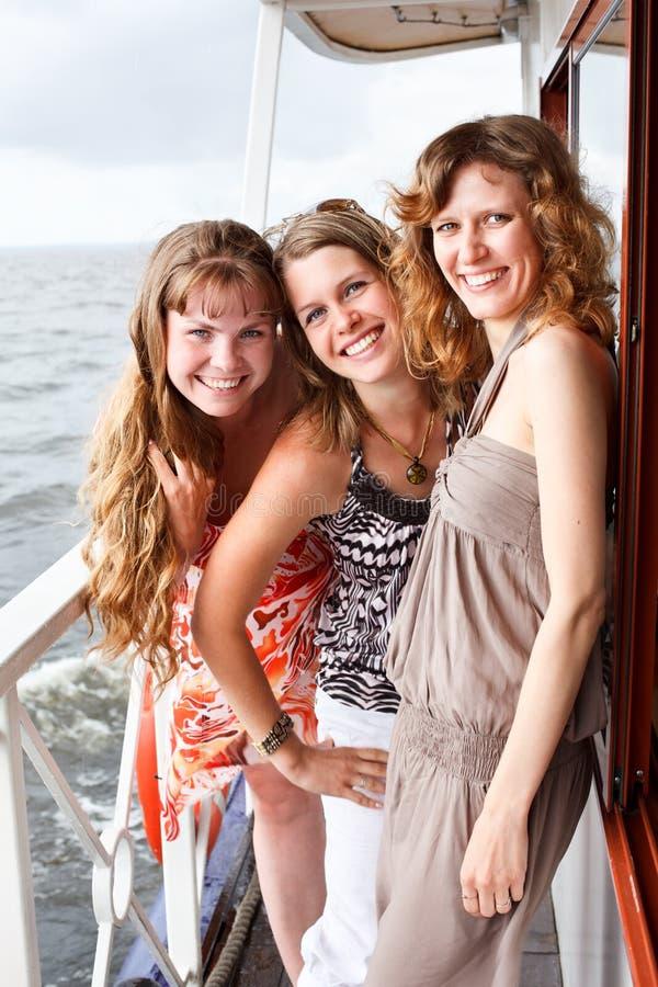 Tre belle giovani femmine sulla piattaforma della nave immagine stock libera da diritti