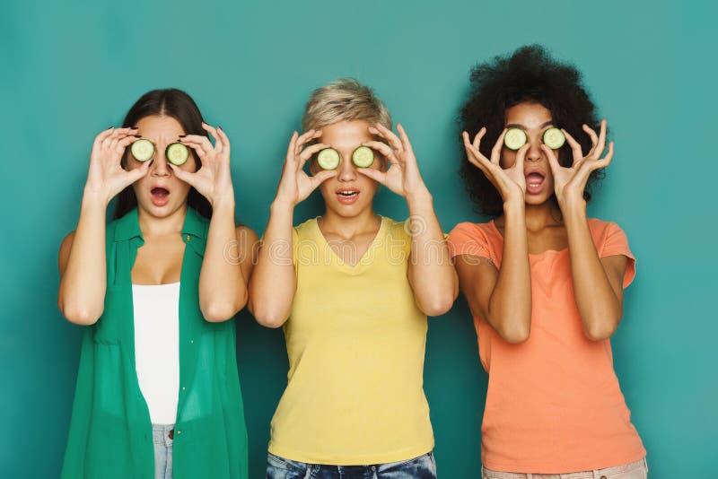 Tre belle ragazze che coprono gli occhi di pezzi del cetriolo fotografie stock libere da diritti