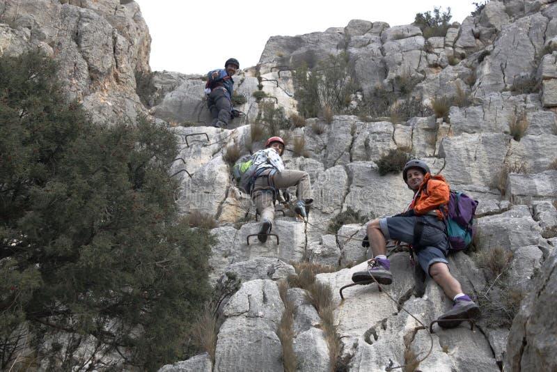 Tre bergsbestigare som gör a via ferrata royaltyfri bild