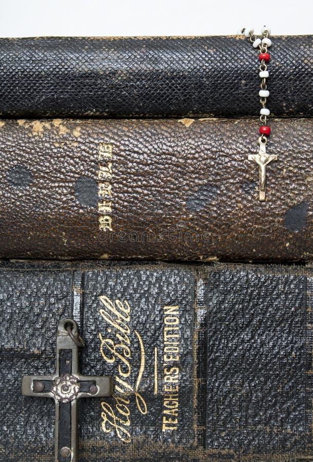 Tre bibbie impilate oggetto d'antiquariato con un rosario antico di due incroci sopra fotografia stock libera da diritti