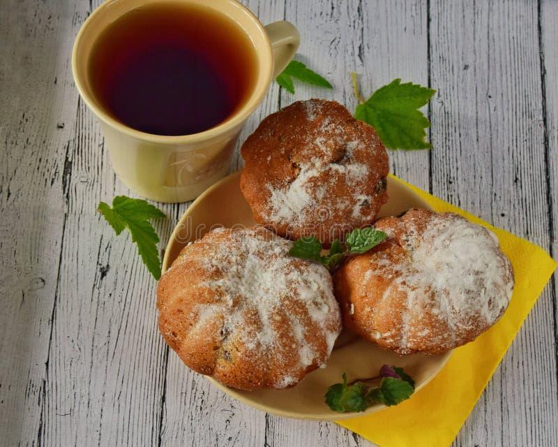 Tre bigné con l'uva passa con il primo piano del tè immagini stock